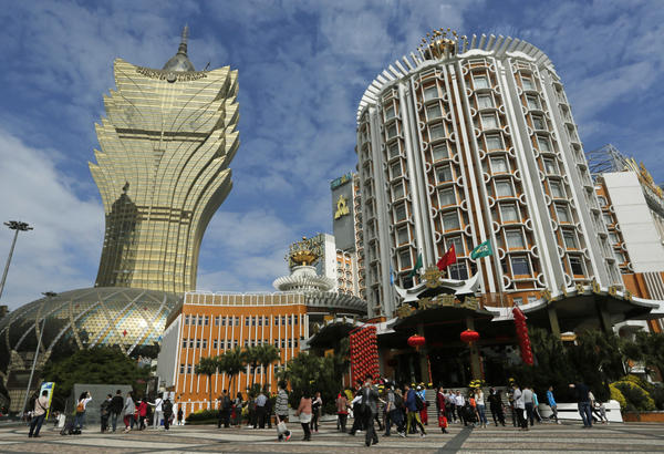 Tourists gather in front of old and new Casino Lisboa during a Chinese New Year celebration in Macau, a special administrative region of China, on Feb. 1. For decades, the Lisboa was the only game in town. Now, the world's biggest gambling companies are scrambling to set up shot in what was once a sleepy Portuguese colony.
