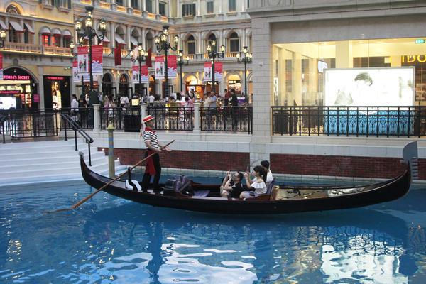 A gondolier serenades tourists at a replica of St. Mark's Square in the Venetian casino in Macau.