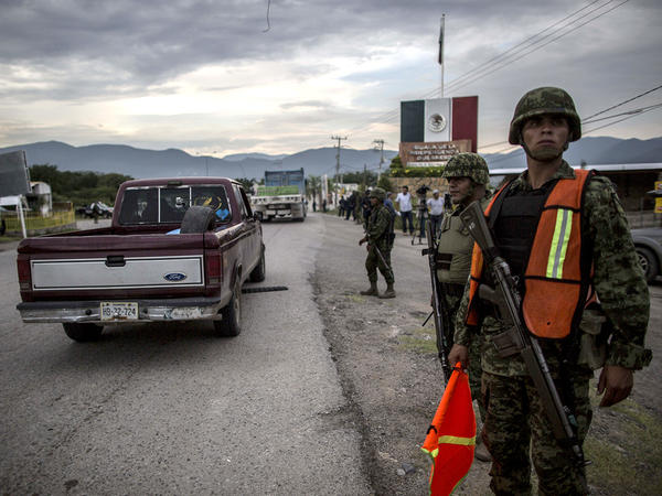 Groups of rural and community police arrive in the city of Iguala on Tuesday to help in the search for 43 students who disappeared after a confrontation with local police on Sept. 26.