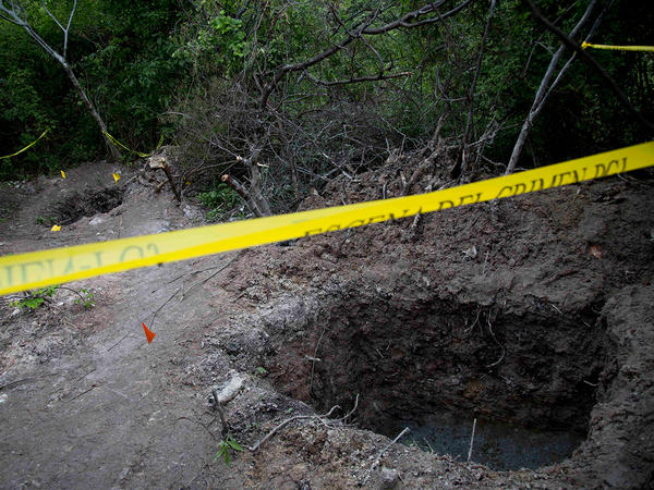 Clandestine graves are seen near Iguala on Monday. State officials have been unable so far to determine whether the 28 bodies found in the graves are of the students who were attacked by local police.