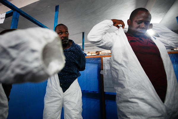 """Eloba trainees, including doctors, nurses and sanitation workers, suit up on their fifth and final day of training and their first """"dress rehearsal"""" before being sent out to Ebola treatment units."""