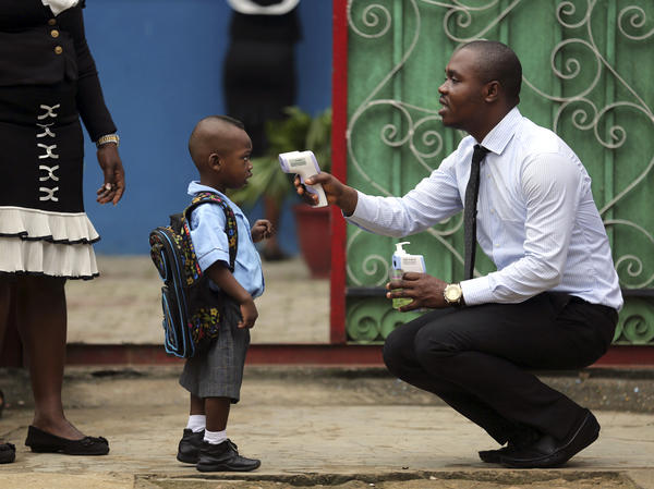 A school official shows a pupil an infrared digital laser thermometer before taking his temperature in Lagos, Nigeria, in September. Starting this week, similar hand-held devices are checking foreheads for fever at some U.S. airports.