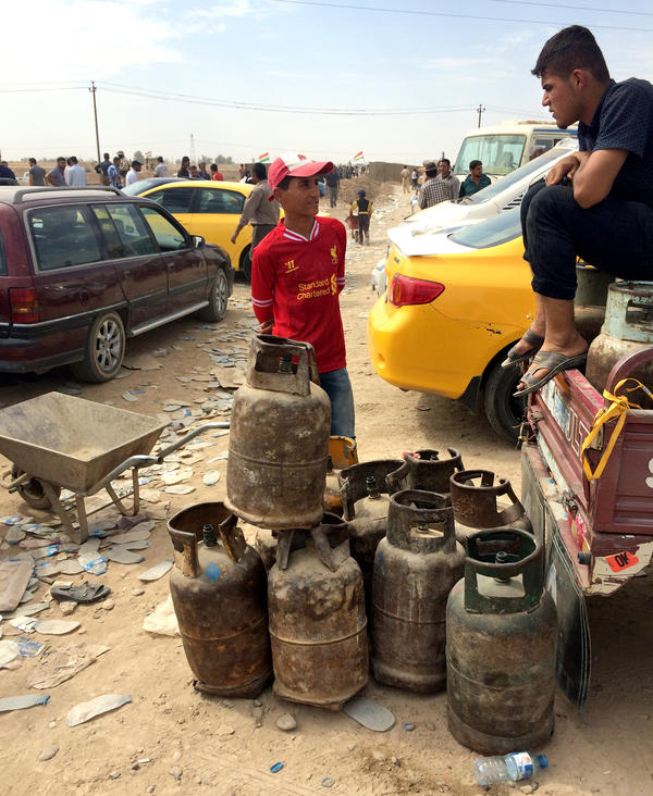 Vendors sell cooking gas to people passing in and out of the checkpoint.