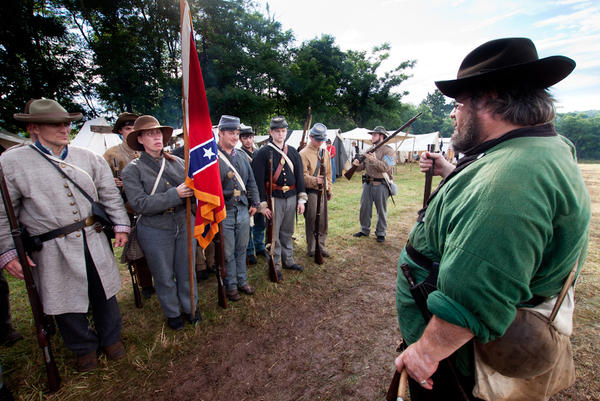 Waverly Adcock, a sergeant and founder of the West Augusta Guard, prepares his company for inspection and battle at a Civil War re-enactment in Virginia. Sara Smith, whose great-great-grandfather was wounded at the Battle of Gettysburg, holds the Confederate battle flag.