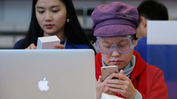 A customer sets up her new iPhone 6 at an Apple store in Beijing on Friday. A group says the Chinese government backed an attack against users of Apple's iCloud service, but the government denies the claim.