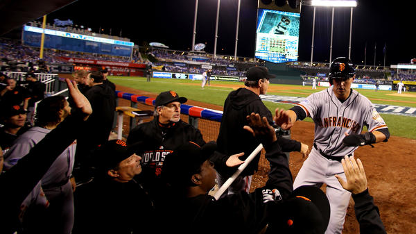 Microphones line the dugout, catching the sound of celebrations like this one by the Giants, after second baseman Joe Panik's seventh-inning score in Game 1.