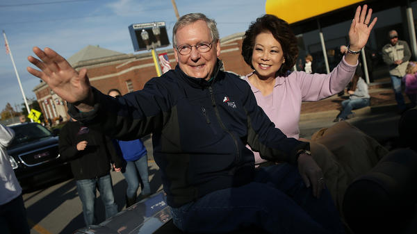 Senate Minority Leader Mitch McConnell of Kentucky waves while riding with his wife Elaine Chao in the Hopkins County Veterans Day Parade on Sunday in Madisonville. McConnell remains locked in a close race with Democratic Senate candidate Alison Lundergan Grimes.