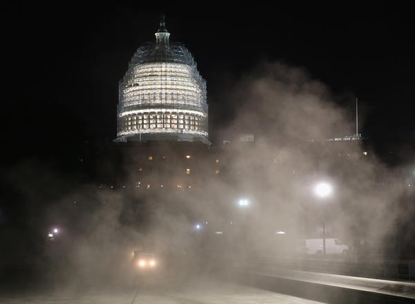 Sweepers stir up dust as they clean the reflecting pool in front of the U.S. Capitol on Tuesday.