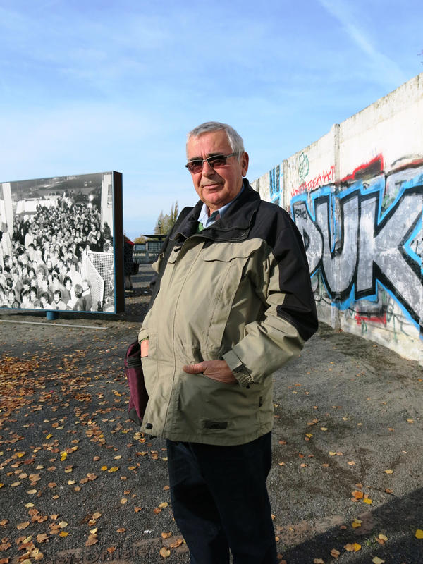Jaeger stands in front of a remnant of the Berlin Wall. Behind him is a photo from Nov. 9, 1989, when he was the border guard who opened up the Bornholmer Street crossing, allowing East Germans to go to the west, the event that marked the fall of the wall.