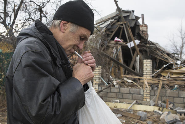 A man smokes next to a bombed out house near Donetsk airport in the city of Donetsk, eastern Ukraine on Sunday.