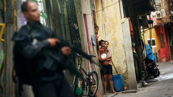 Residents look on as Brazilian military police officers patrol Mare, one of the largest complexes of favelas in Rio de Janeiro, Brazil, on March 30. In one of the world's most violent countries, homicide rates are dropping — but only for whites.