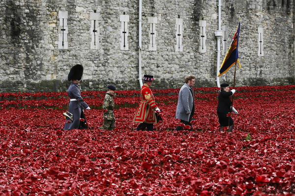 """Servicemen and artist Paul Cummins (second from right) walk past his art installation """"Blood Swept Lands and Seas of Red,"""" made of ceramic poppies, during an Armistice Day ceremony at the Tower of London on Tuesday."""