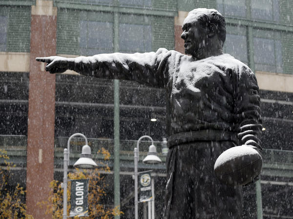The Curly Lambeau statue at Lambeau Field in Green Bay, Wis., gets coated in snow on Monday.