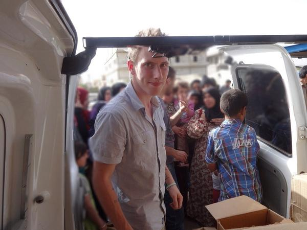 Abdul-Rahman Kassig, who was formerly known as Peter, is shown with a truck filled with aid supplies for Syrian refugees. The American aid worker was seized by the Islamic State in October 2013 and subsequently killed by the group, which released a video Sunday of his beheading.