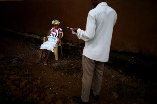 Surveillance team member Osman Sow talks with Kadiatu, who is eight months pregnant and suspected of having Ebola. Survey teams canvas the community every day to assess sick people and dispatch burial teams to collect the dead.