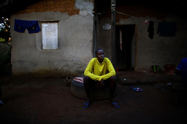 Alusine Banguar, 15, sits outside his home to explain his symptoms to a surveillance officer.
