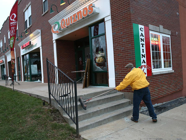 A worker cleans up glass outside a Quiznos restaurant that was damaged during a demonstration Tuesday in Ferguson, Mo.