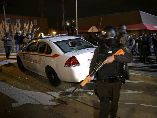 A police officer in Ferguson, Mo., stands guard as protests turned violent following Monday night's announcement of the grand jury's decision not to indict police officer Darren Wilson in the shooting death of 18-year-old Michael Brown.