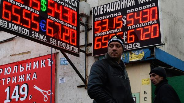 Pedestrians walk past a board listing foreign currency rates against the Russian ruble in Moscow on Wednesday. The ruble was trading at about 35 to the U.S. dollar this summer. Now it's more than 50 rubles to the dollar and the currency has been hitting record lows recently.