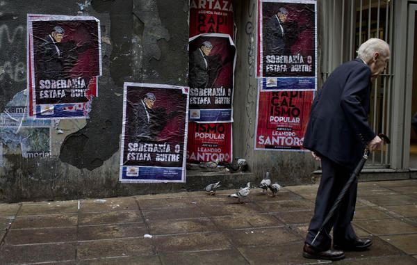 "A wall in Buenos Aires, Argentina, displays posters with an image of U.S. Judge Thomas Griesa and a message in Spanish — ""Sovereignty or vulture scam"" — in support of Argentina's government in its dispute against a U.S. hedge fund, known locally as a ""vulture fund."""