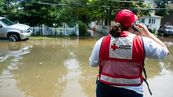 An American Red Cross worker stands on an inundated Brooke Avenue following heavy rains and flash flooding Aug. 13, in Bay Shore, N.Y.