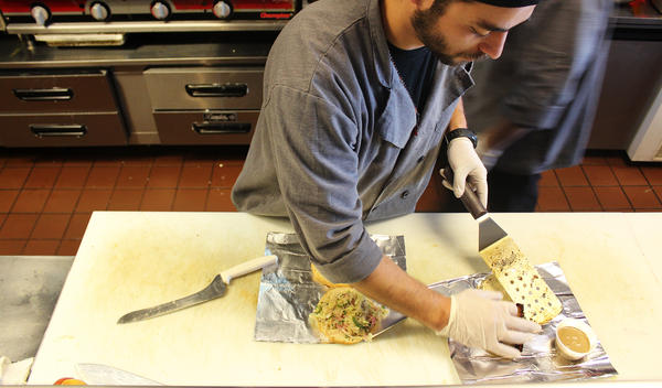 A worker at Moo Cluck Moo, a fast-casual burger and chicken chain in suburban Detroit, prepares a meal. Workers at Moo Cluck Moo all make $15 an hour.