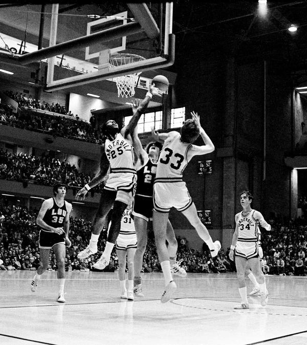 Perry Wallace, playing for Vanderbilt University, blocks the shot of 'Pistol' Pete Maravich, circa 1970.