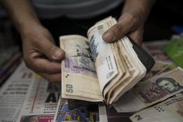 A newsstand owner counts Argentine pesos in Buenos Aires. Many Argentines carry large amounts of cash, saying they do not trust banks. This has contributed to a surge in robberies.