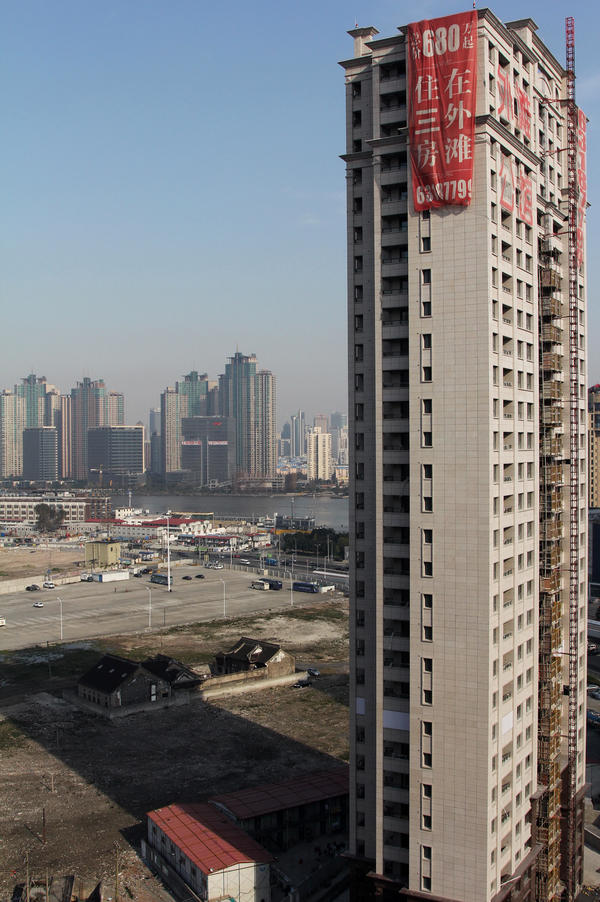 A luxury apartment tower rises near Shanghai's Huangpu River. Chen, an underground Christian who has sent his family to Los Angeles, hopes his home will be knocked down to make way for buildings like this one across the street, so Chen can use the compensation to buy a house in suburban LA.