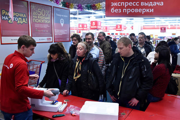 Customers line up at an electronics store in Moscow on Monday. With the value of Russia's ruble declining rapidly, prices are expected to soar, and many shoppers are frantically spending their money on electronics, furniture and even cars.