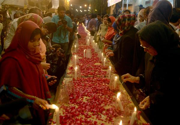 Pakistani activists from the Muttahida Qaumi Movement light candles in Karachi on Tuesday for the victims of the Taliban's attack.