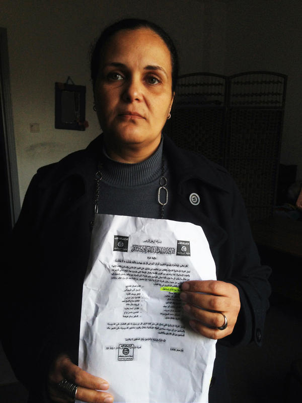 Donia al-Amal Ismael is a poet and women's rights activist in Gaza. She holds a flier purportedly from ISIS, the militant group, that accused her and other writers of criticizing God and Islam and threatening them. A second, later flier said ISIS was not responsible for the earlier threats.