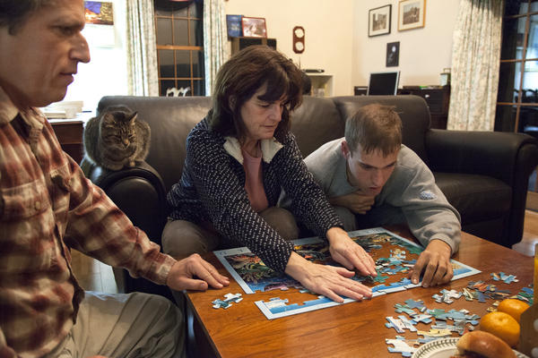Mike Tranfaglia works on a puzzle with Katie and their son Andy. The parents started a foundation to fund research in treatments for fragile X.