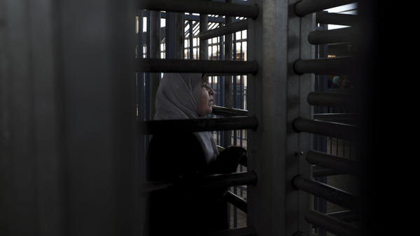 A Palestinian woman waits to cross the Qalandiya checkpoint between Jerusalem and the West Bank city of Ramallah in 2010.