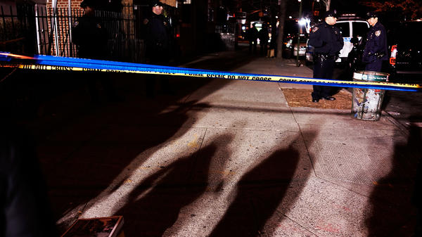 Police officers surround the area where two New York City police officers were killed Saturday afternoon as they sat in their marked police car on a Brooklyn street corner.