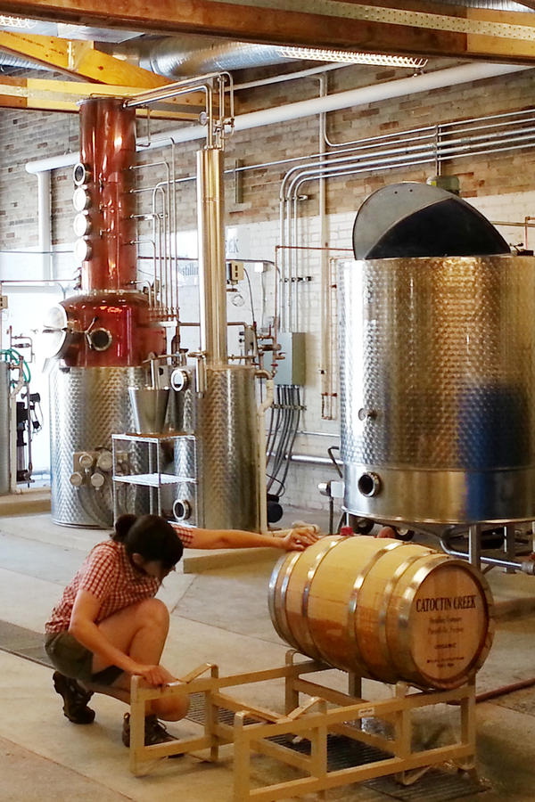 The pot stills and mash tun at Catoctin Creek distillery in Old Town Purcellville, Va. Becky Harris, co-founder of the distillery, checks a barrel for leaks.