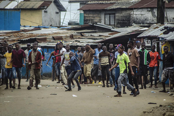 Angry protesters hurl rocks at the soldiers and policemen enforcing the quarantine.