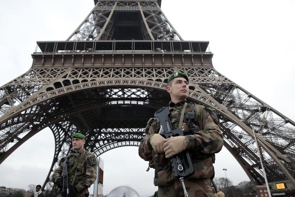 French soldiers patrol in front of the Eiffel Tower on Wednesday, after heavily armed gunmen stormed the offices of <em>Charlie Hebdo</em> and killed at least 12 people — the deadliest attack in France in four decades.