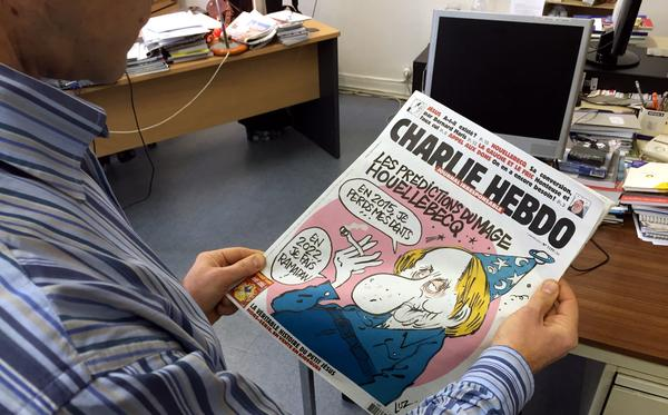 A journalist views the front page of the latest issue of <em>Charlie Hebdo</em> on Wednesday.