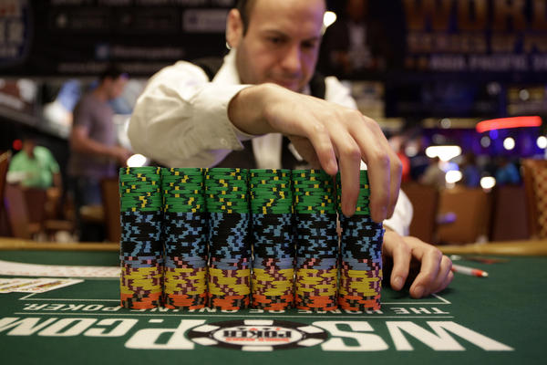 Dealer Omar Abu-Eid adjusts a stack of chips before the first day of the World Series of Poker's main event in Las Vegas last July. Humans still reign in most versions of poker. Whew.
