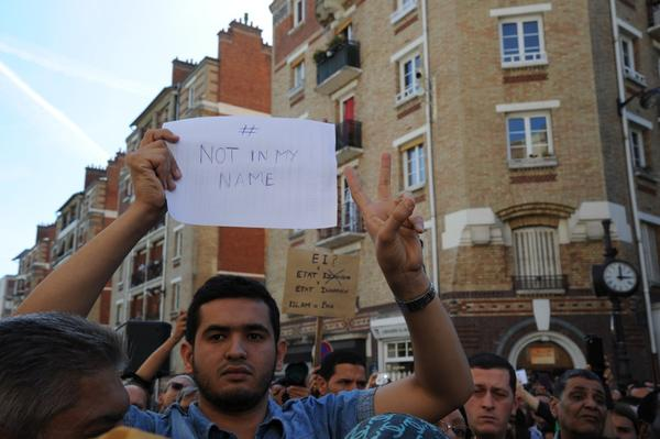 A man holds a placard reading 'Not in my name' during a demonstration called by Muslim groups to denounce the 'barbarism' of Islamic State militants, on September 26, 2014 outside Paris's main mosque, two days after the beheading of a French national by jihadists aligned to the group in Algeria. (Dominique Faget/AFP/Getty Images)