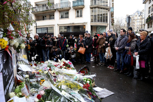 Flowers are left close to the Charlie Hebdo offices on a day of mourning following a terrorist attack at the satirical newspaper building on January 8 in Paris, France. Twelve people were killed including two police officers as two gunmen opened fire at the offices of the French satirical publication Charlie Hebdo on January 7.  (Marc Piasecki/Getty Images)