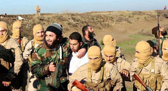 Islamic State militants captured Moath al-Kasasbeh on Dec. 24 after his warplane went down in Syria. This image posted by the Raqqa Media Center shows militants with al-Kasasbeh, wearing the white shirt, in Raqqa, Syria.