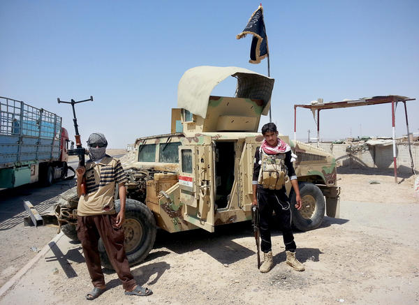 Militants of the Islamic State stand with a captured Iraqi army Humvee outside Baiji oil refinery, north of Baghdad, in June 2014. While there is increased radicalization in many parts of the Arab world, there are also groups and individuals working to deradicalize young Muslim men.