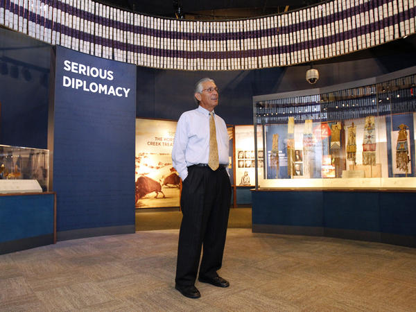 "Kevin Gover, director of the National Museum of the American Indian, stands inside the ""Nation to Nation"" exhibit."