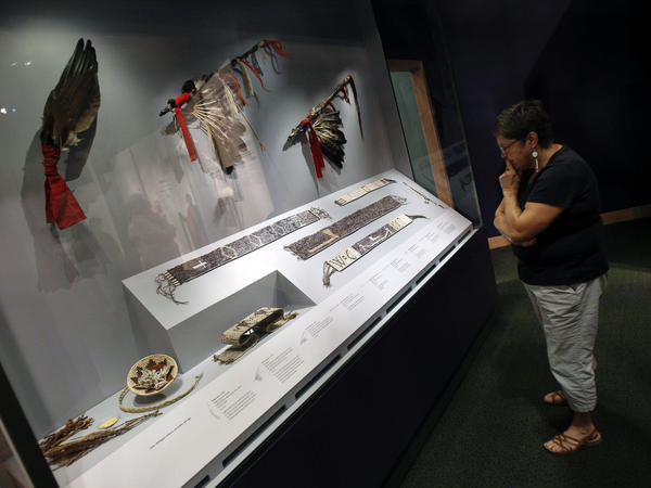 A museum visitor views wampum belts, fans and other diplomatic tools used during the treaty-making process.