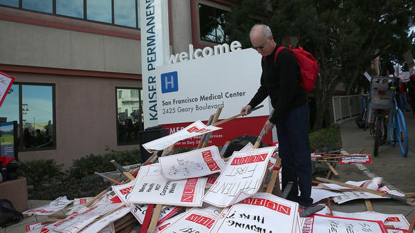 A Kaiser mental health worker with the National Union of Healthcare Workers looks through a pile of signs Monday during day one of a week-long demonstration outside of a Kaiser Permanente hospital in San Francisco.