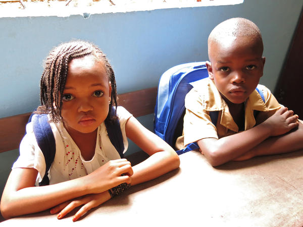 Six-year old Hadja Sow (left) and a classmate on their first day back at school after a prolonged break because of Ebola.