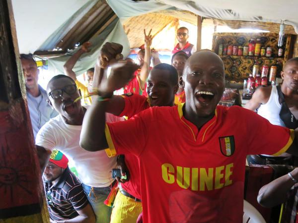Fans in a makeshift sports bar in Conakry celebrate when Guinea scores a goal.