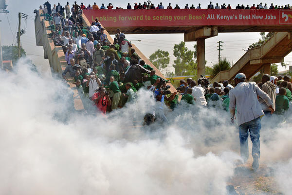 Schoolchildren and activists scramble up a bridge Monday after police try to break up a protest with tear gas at the Langata Road Primary School in Nairobi, Kenya.